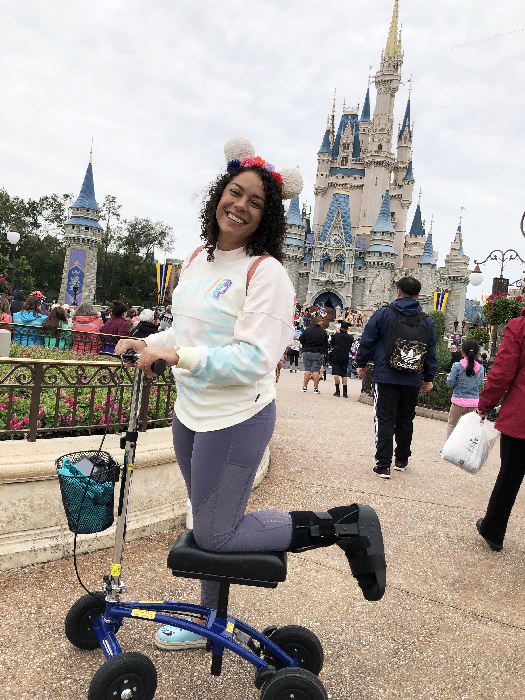 smiling woman riding a knee scooter with cinderella castle in the background