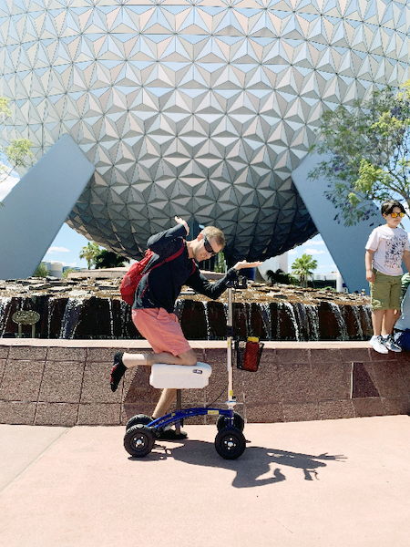 Man riding a knee scooter at Epcot