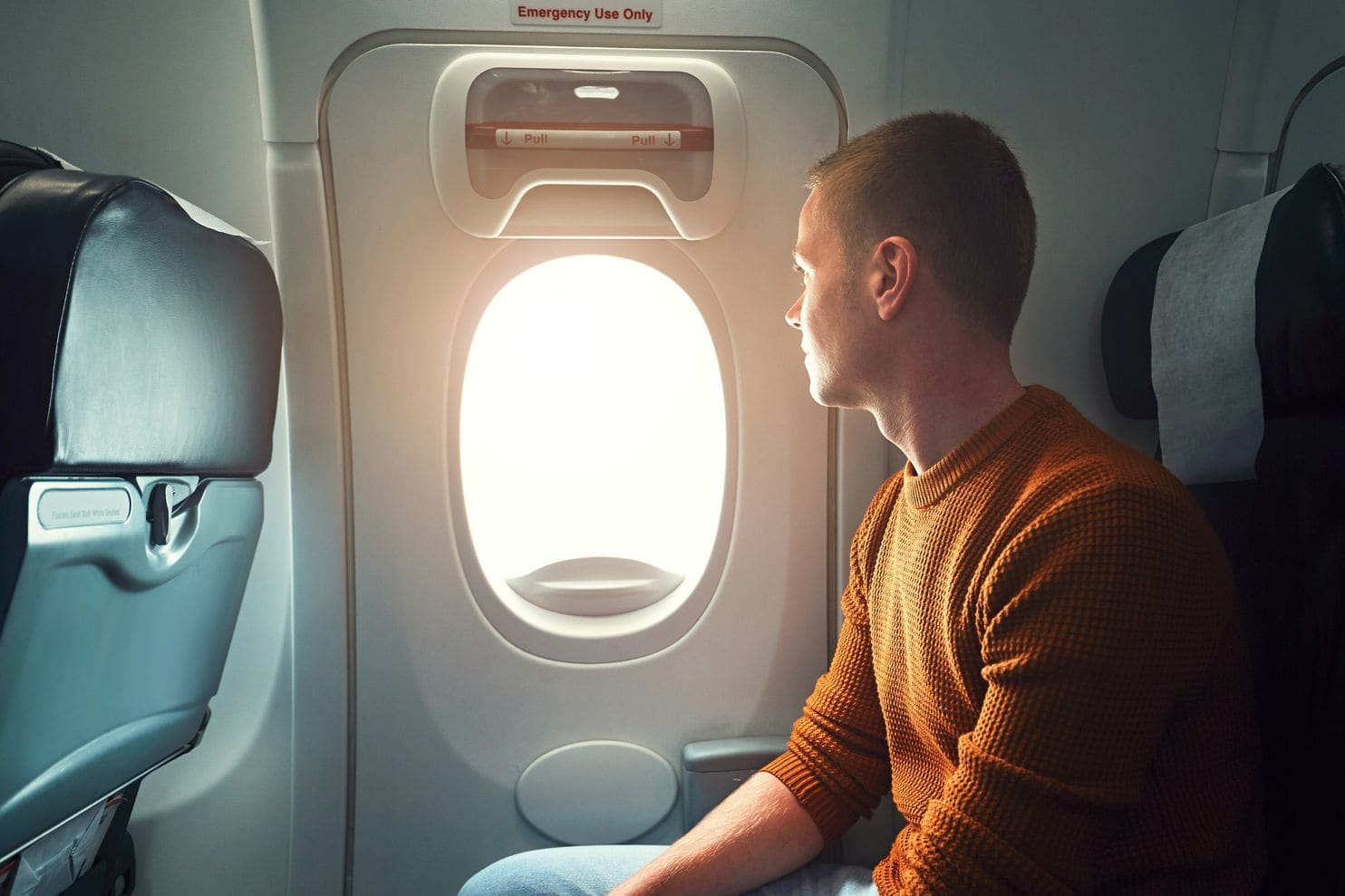 man looking out plane window