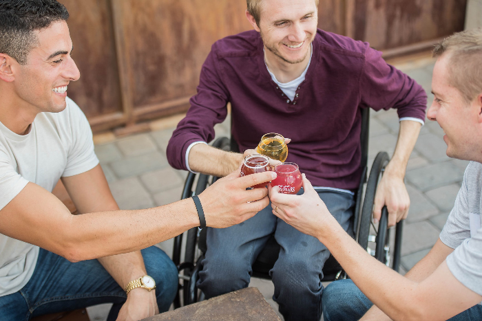 person in wheelchair drinking beer with friends