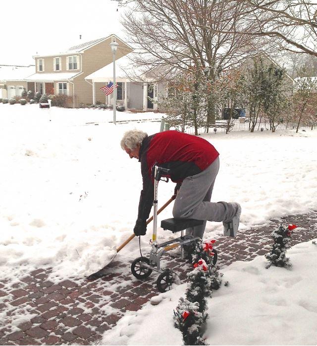 Man shoveling snow on knee scooter