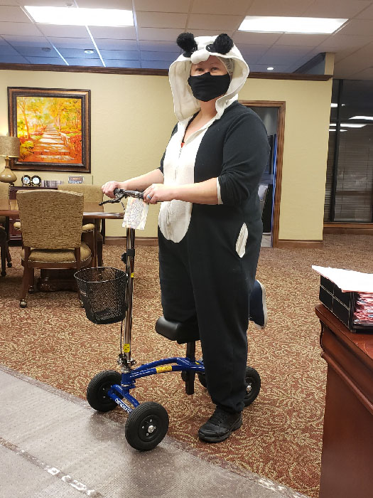 woman with a panda costume riding a knee scooter