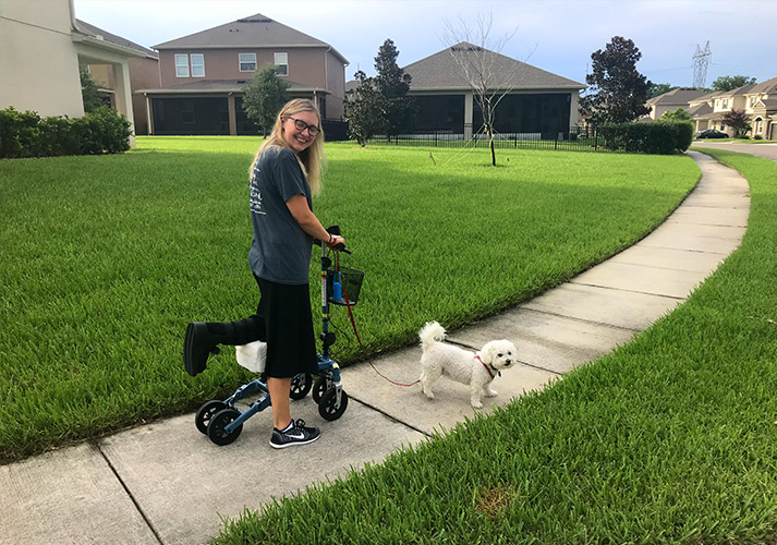 lady using a knee scooter and walking her dog