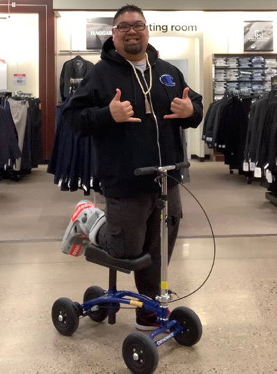 man shopping on a knee scooter