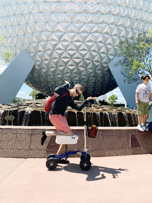 Man posing with a knee scooter in front of Epcot ball