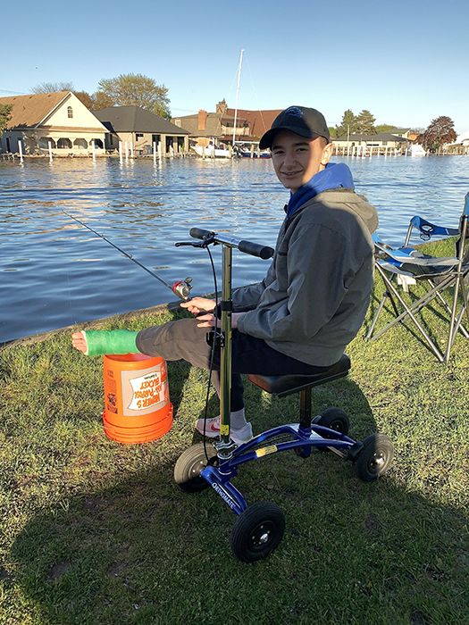kid fishing sitting on a knee scooter