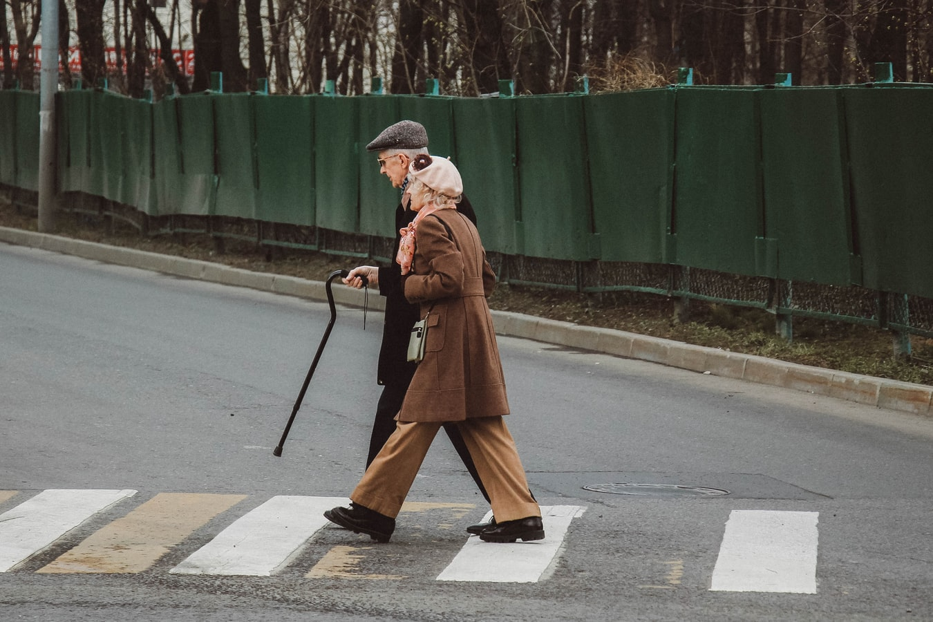 man and woman walking with cane